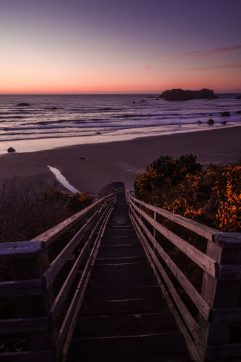 Scenic view steps by sea against sky during sunset