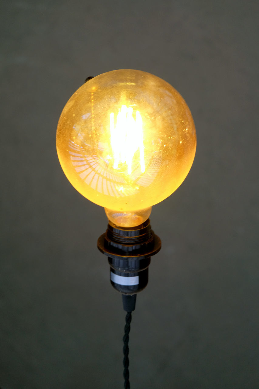 lighting equipment, illuminated, close-up, yellow, light bulb, electricity, no people, indoors, electric light, focus on foreground, orange color, glowing, light, single object, light - natural phenomenon, studio shot, fuel and power generation, electric lamp, still life, electrical equipment