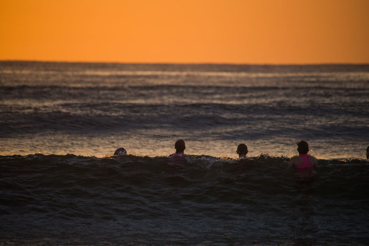 Friends swimming in sea against sky during sunset
