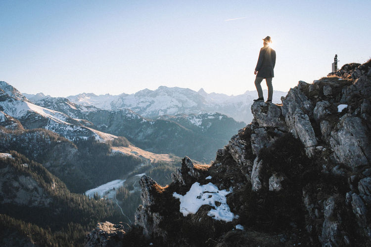 Low angle view of man standing on rocky mountains against clear sky during sunny day