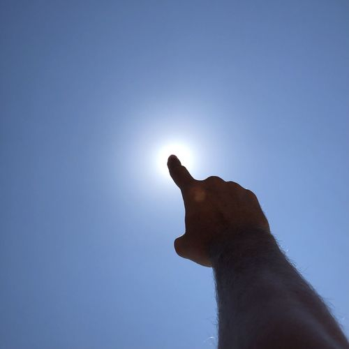 Low angle view of hand against clear sky