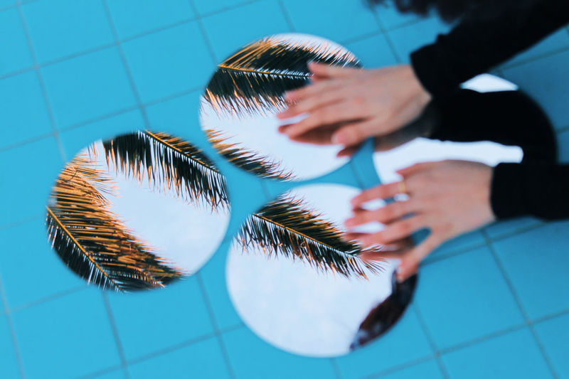 Cropped hands touching mirrors with reflection of palm trees