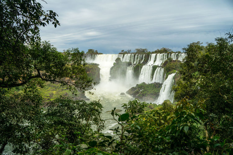 Scenic view of waterfall against sky in iguazu