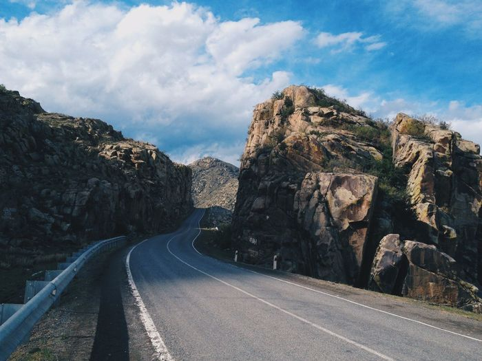 Empty road amidst rocks against sky