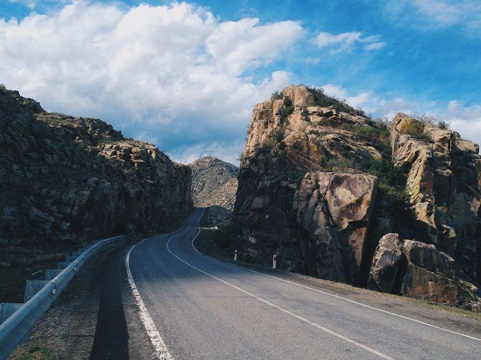 Empty road amidst rocks against sky. altai