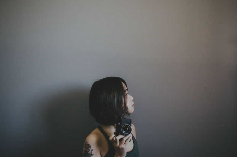 Woman holding camera while standing by wall