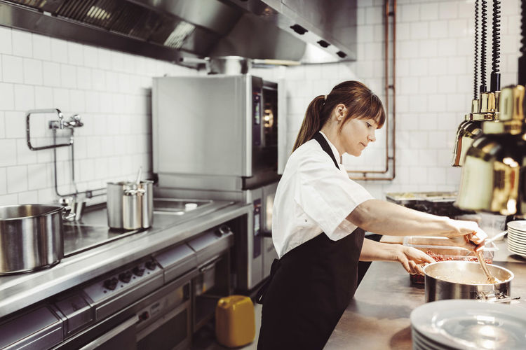 Side view of woman preparing food in restaurant