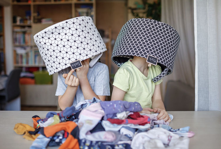 Cute kids with basket on head at home