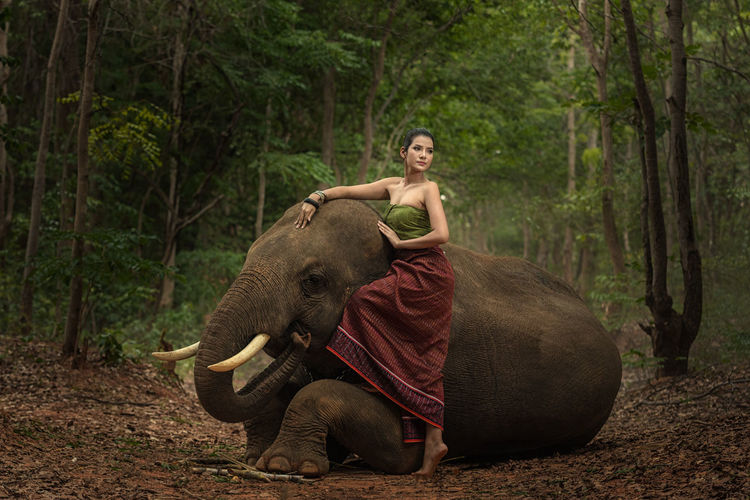 Woman with elephant standing outdoors
