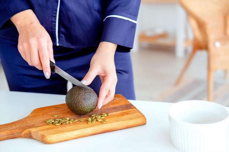 Girl in pajamas prepares breakfast. proper nutrition. the girl makes a salad of avocado