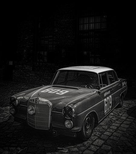 Vintage car on street against buildings at night