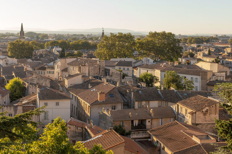 Wide view of rooftops of old city of Avignon, France Architecture Avignon Building Exterior Built Structure City Cityscape Community Day Elevated View Horizon Over Land House Human Settlement Landscape Outdoors Residential District Roof Rooftop Sky Town Travel Destination Tree