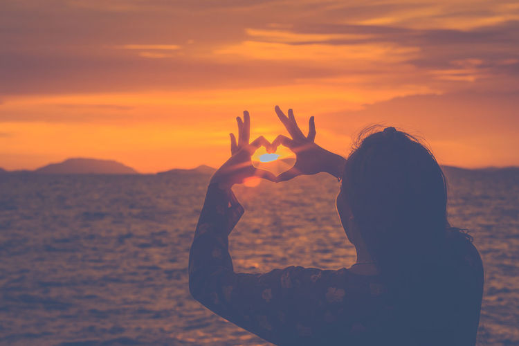 Woman making heart shape towards sun while standing by sea during sunset