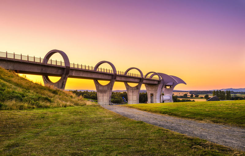 Arch bridge on field against sky during sunset