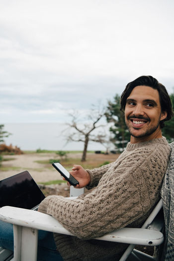 Portrait of smiling young man using smart phone against sky