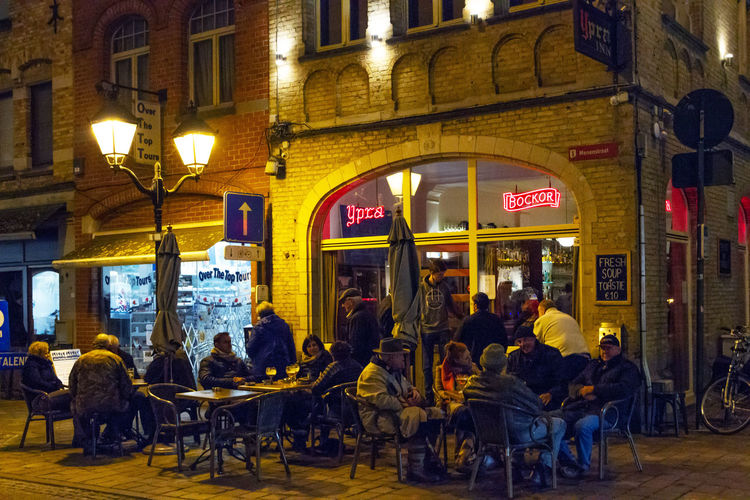Illuminated Group Of People Architecture City Restaurant Cafe Real People Table Seat Building Exterior Built Structure Street Chair Large Group Of People Men Sitting Business Women Night Adult Outdoors Light