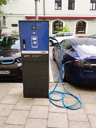 Ellektroauto beim Aufladen des. Akku, Tesla, Stadt, Strom, Energie, tanken, Laden, Ladestation, Ladekabel, auftanken, Accu Battery Loading Dock Tesla Electric Car Electro Electricity  EyeEm Selects Fuel And Power Generation Day No People Refueling Communication Connection Fuel Pump Technology Outdoors Cable Filling Car Gas Station Electricity