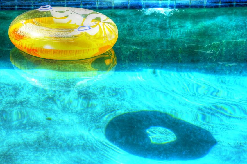 Innertube floating in a blue pool signifying the beauty of summer. Blue Day Floating On Water Innertube No People P Reflection Summer Summertime Tranquil Scene Tranquility Vibrant Color Water Water Reflections Water Surface