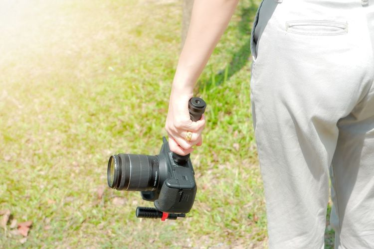 Midsection of man holding camera while standing by grass