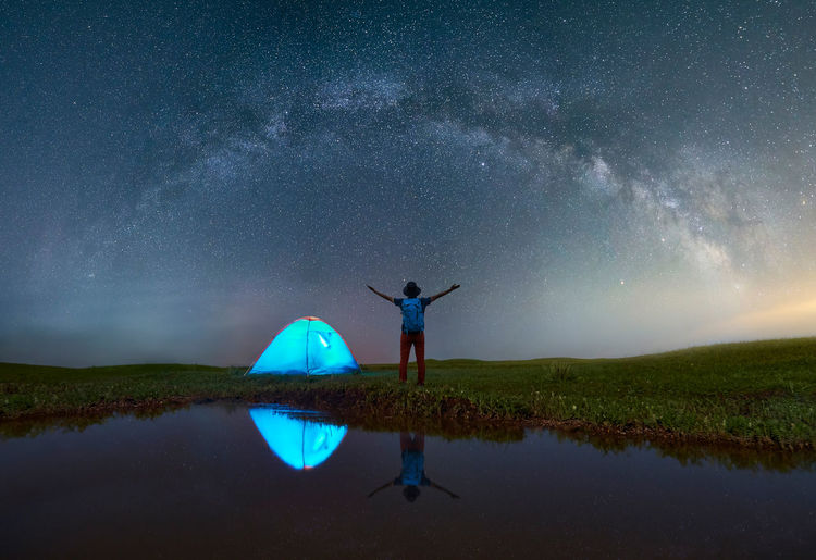 Milky Way over the grasslands Galaxy Travel Traveling Arms Raised Beauty In Nature China Human Arm Leisure Activity Lifestyles Men Nature Night One Person Rear View Reflection Scenics - Nature Space Standing Star Star - Space Star Field Tent Tranquil Scene Travel Destinations Water