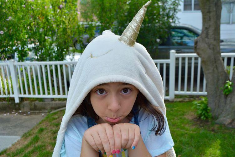 Portrait of cute girl wearing gesturing while wearing unicorn costume in yard