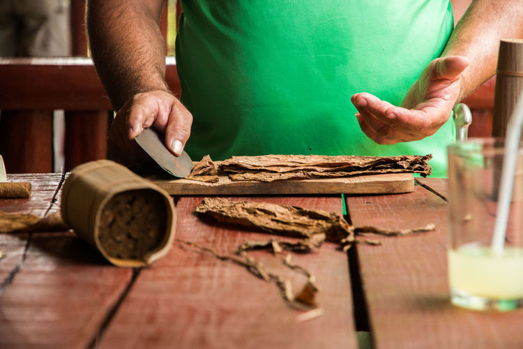 Close-Up Of Man Making Cigar