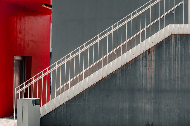 Red railing by wall of building