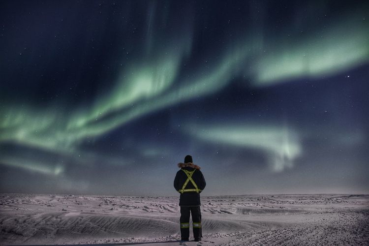 Man Looking At Northern Light While Standing On Snowcapped Landscape