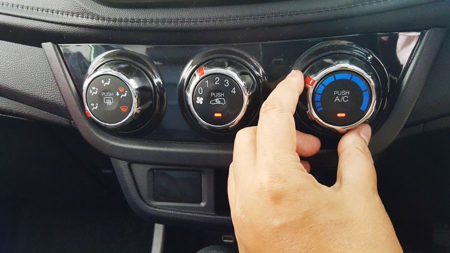 Cropped hand adjusting air conditioner in car