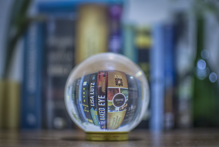 crystal ball Close-up No People Focus On Foreground Selective Focus Text Shape Table Day Reflection Circle Still Life Glass - Material Communication Design Finance Architecture Crystal Ball Photography Lensball Bookshelf Reflection Upside Down See Through Books Indoor Home