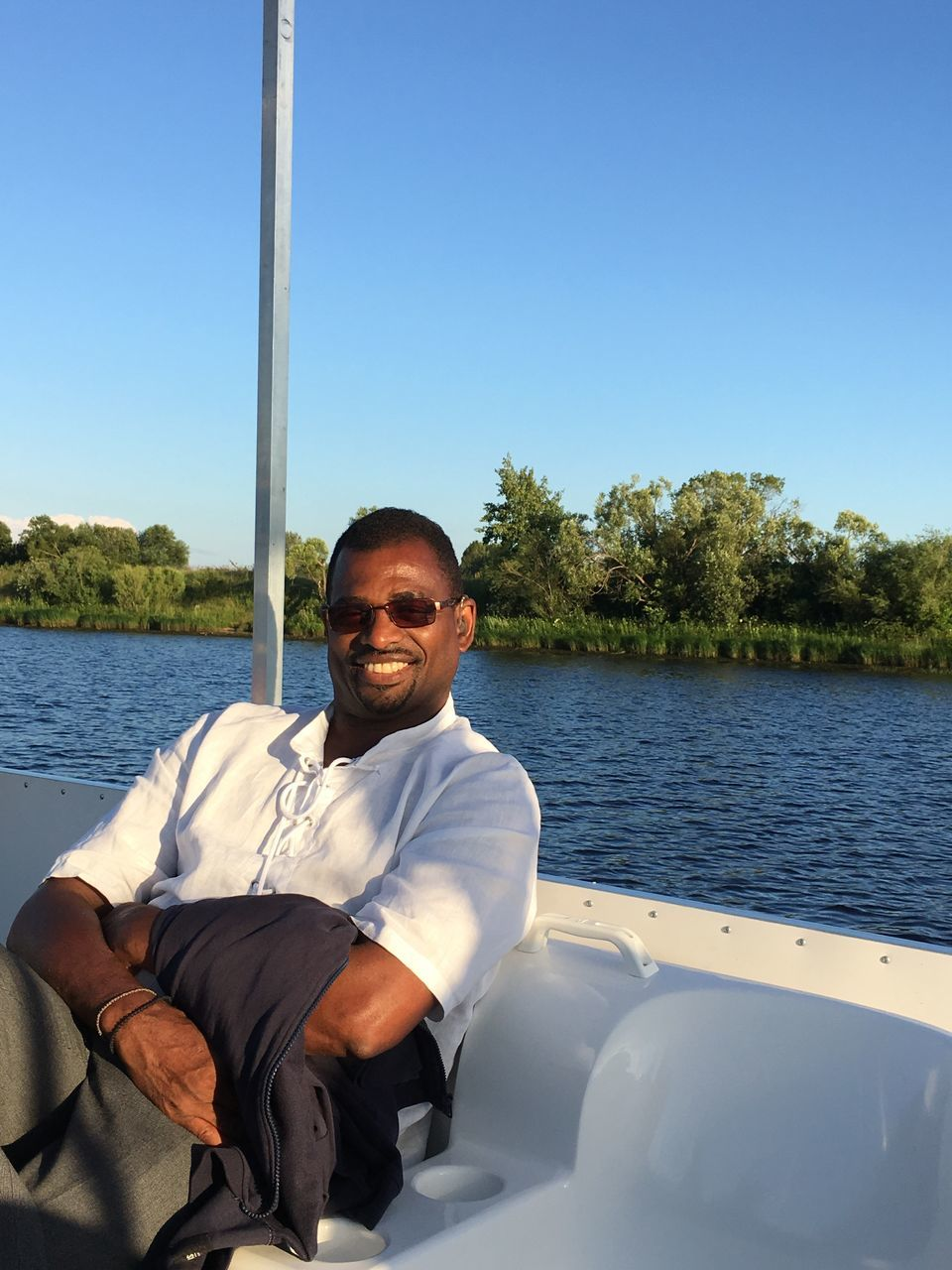 real people, one person, water, looking at camera, river, leisure activity, mode of transport, portrait, day, sailing, mid adult men, outdoors, transportation, lifestyles, nautical vessel, casual clothing, sitting, nature, smiling, clear sky, happiness, standing, young adult, tree, beauty in nature, sky