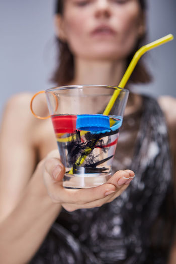 Midsection of young woman holding drinking glass with plastics
