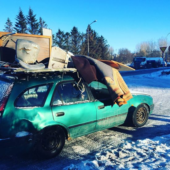 Abandoned car against blue sky