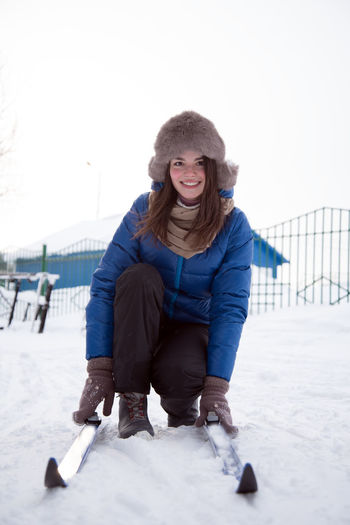 Portrait of young woman with skies on snow covered land