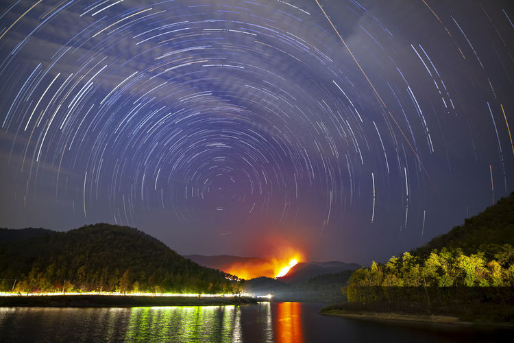 Star trails and wild fire at night time