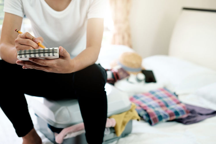Midsection of woman writing in book while sitting on bed at home