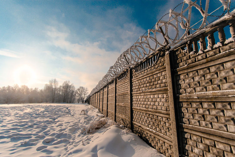 Barbed Wire Beauty In Nature Border Brick Wall Cold Temperature Day Nature No People Outdoors Prison Sky Snow Wall Winter