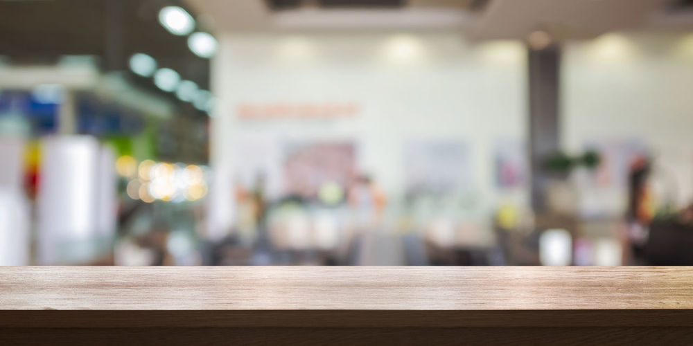 Empty wooden table top with blurred store background. Blurred Copy Space Absence Bar Counter Blank Business Cafe Day Defocused Desk Display Education Empty Focus On Foreground Food And Drink Food And Drink Industry Furniture In A Row Indoors  No People Restaurant Shelf Table Tabletop Wood - Material
