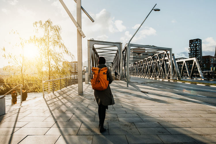 Rear view of woman carrying backpack while walking on bridge