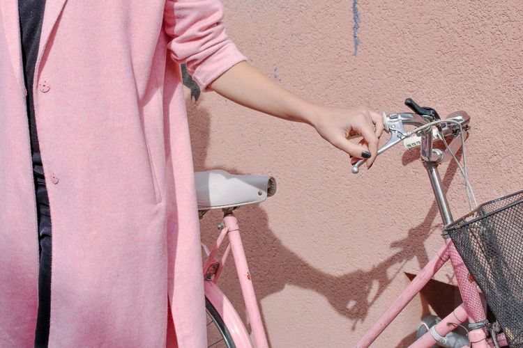 Midsection Of Woman Standing By Bicycle Against Wall