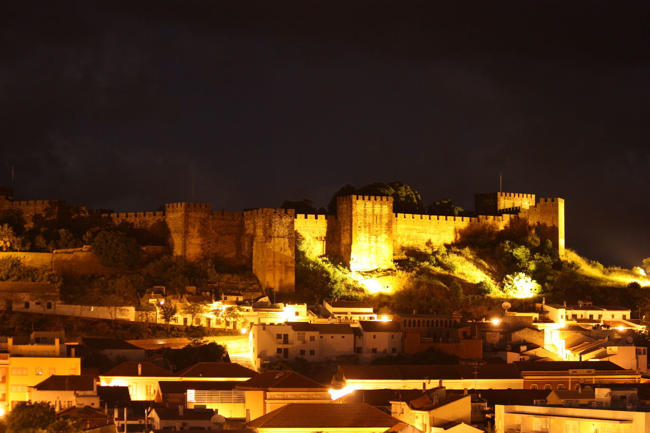 Illuminated Houses Against Castle At Night
