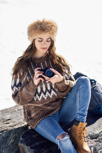 Beautiful young woman using smart phone while standing outdoors