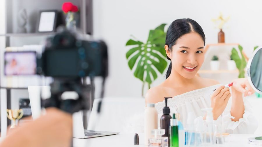 Portrait of smiling woman holding camera on table