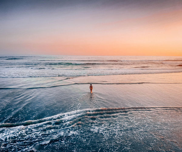 Woman wading in sea against sky during sunset
