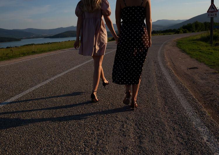 Rear view of women walking on road