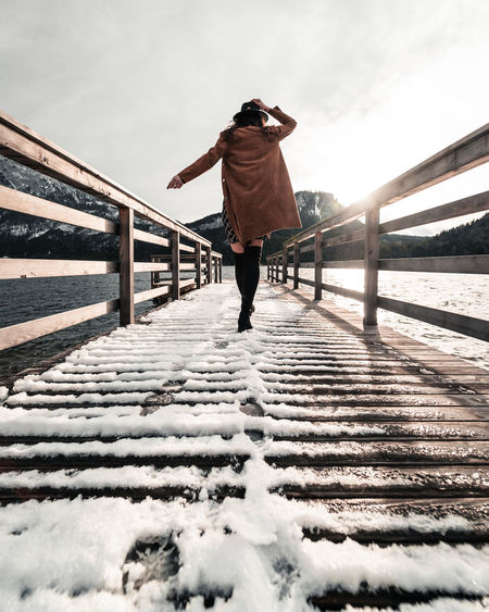 Rear view of woman walking on footbridge during winter