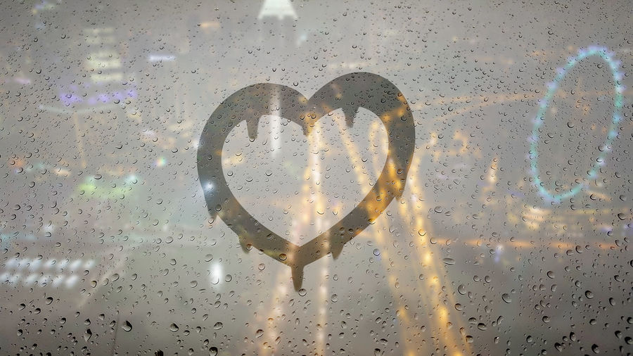 Draw a heart shape by hand on a glass of water droplets with night cityscape background. Heart Shape Love Positive Emotion Emotion Text No People Glass - Material Close-up Western Script Communication Creativity Indoors  Transparent Multi Colored Design Wet Shape Full Frame Graffiti Message Cityscape Sign Valentine's Day  RainDrop Water