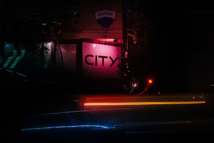 Illuminated road sign on street in city at night