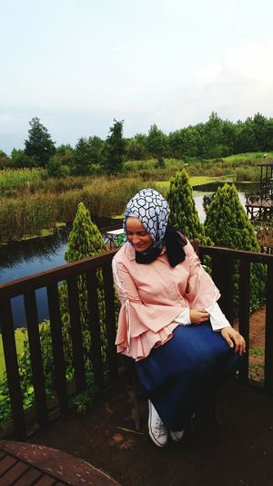 Woman In Hijab Sitting By Railing Against Trees And Lake