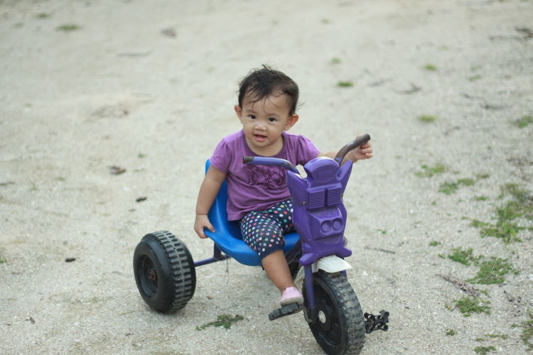 Portrait Of Cute Girl Sitting On Tricycle